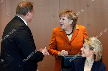 German Chancellor Angela Merkel, center, chats with German Minster of Economic Cooperation and Development Dirk Niebel, left, and German Labor Minister Ursula von der Leyen, right, at the beginning of the weekly cabinet meeting at the chancellery in Berlin, Germany