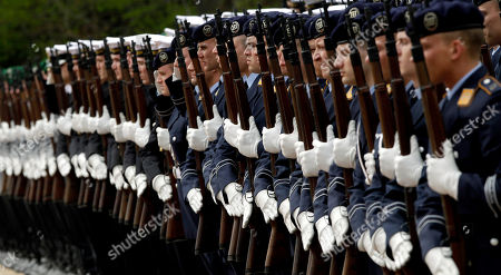 Soldiers of the guard battalion hold up their rifles during a military welcome ceremony of German President Joachim Gauck, unseen, for King Letsie III. of Lesotho, right, at the Bellevue Palace in Berlin, Germany