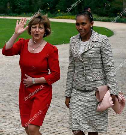 Daniela Schadt, left, partner of German President Joachim Gauck, unseen, and Masenate Mohato Seeiso, right, wife of King Letsie III. of Lesotho, unseen, walk past the photographers after a military welcome ceremony at the Bellevue Palace in Berlin, Germany