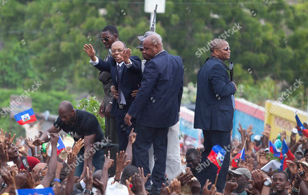 Jean-Bertrand Aristide Flanked by body guards, former Haitian President Jean-Bertrand Aristide greets supporters as leaves the courthouse in Port-au-Prince, Haiti, . Aristide greeted a small group of onlookers after testifying before a judge investigating the slaying of one of the country's most prominent journalists. The judge is questioning Aristide about the killing in April 2000 of Jean Dominique, a friend of the former president