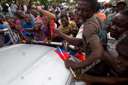 Stock Picture of Supporters of former Haitian President Jean Bertrand Aristide crowd around his car as he slowly drives away from the courthouse in Port-au-Prince, Haiti. . In a rare public appearance, Aristide greeted a small group of onlookers after testifying before a judge investigating the slaying of one of the country's most prominent journalists. The judge is questioning Aristide about the killing in April 2000 of Jean Dominique, a friend of the former president