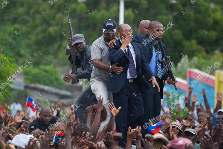 Stock Image of Jean Bertrand Aristide Flanked by body guards, former Haitian President Jean-Bertrand Aristide, center, greets supporters as leaves the courthouse in Port-au-Prince, Haiti, . Aristide greeted a small group of onlookers after testifying before a judge investigating the slaying of one of the country's most prominent journalists. The judge is questioning Aristide about the killing in April 2000 of Jean Dominique, a friend of the former president