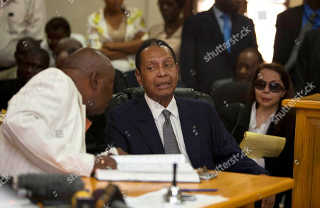 """Jean-Claude Duvalier, Veronique Roy Former Haitian dictator Jean-Claude Duvalier, known as """"Baby Doc,"""" center, attends his hearing as his companion Veronique Roy sits behind, right, inside a courthouse in Port-au-Prince, Haiti, . Duvalier appeared in court Thursday after three times shunning a summons for a hearing on whether he should be charged with human rights abuses during his brutal 1971-1986 regime. Next to him sat his defense attorneys and his longtime partner, who did not remove her sunglasses during the proceedings"""