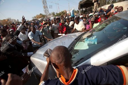 """Jean-Claude Duvalier Supporters of former Haitian dictator Jean-Claude Duvalier, known as """"Baby Doc,"""" surround his car as he leaves the court after attending his hearing in Port-au-Prince, Haiti, . Duvalier appeared in court Thursday after three times shunning a summons for a hearing on whether he should be charged with human rights abuses during his brutal 1971-1986 regime"""