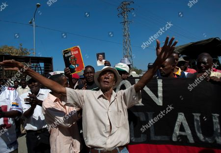Supporters of former Haitian dictator Jean-Claude Duvalier demonstrate outside the courthouse where Duvalier attends a hearing in Port-au-Prince, Haiti, . Duvalier appeared in court Thursday after three times shunning a summons for a hearing on whether he should be charged with human rights abuses during his brutal 1971-1986 regime