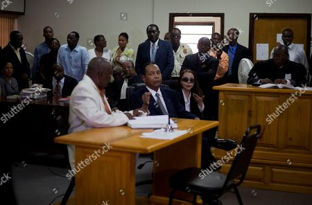 """Jean-Claude Duvalier, Veronique Roy Former Haitian dictator Jean-Claude Duvalier, known as """"Baby Doc,"""" center, attends his hearing as his companion Veronique Roy sits behind, right, inside a courthouse in Port-au-Prince, Haiti, . Duvalier appeared in court Thursday after three times shunning a summons for a hearing on whether he should be charged with human rights abuses during his brutal 1971-1986 regime"""