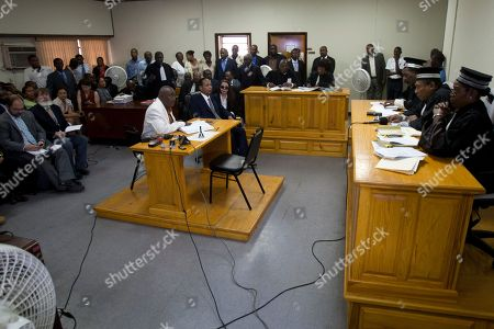 """Jean-Claude Duvalier, Veronique Roy Former Haitian dictator Jean-Claude Duvalier, """"Baby Doc,"""" sitting on end of the desk at center, attends his hearing at court, as his companion Veronique Roy sits to his right in Port-au-Prince, Haiti, . Dozens of supporters cheered as Duvalier emerged wearing a navy blue suit and gray tie and sat facing the three-judge panel. Next to him sat his defense attorneys and his longtime partner, who did not remove her sunglasses during the proceedings. Duvalier is in in court for a hearing on whether he should be charged with human rights abuses during his brutal 1971-1986 regime"""