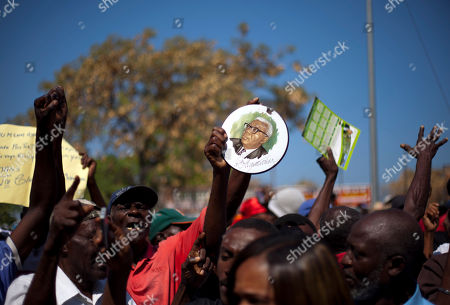 """A supporter of former Haitian dictator Jean-Claude Duvalier, known as """"Baby Doc,"""" holds up a picture of his father, Francois Duvalier, known as """"Papa Doc,"""" outside a courthouse where Jean-Claude attends a hearing in Port-au-Prince, Haiti, . Duvalier is at court Thursday for a hearing on whether he should be charged with human rights abuses during his brutal 1971-1986 regime"""