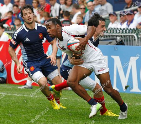 Carlin Isles, Vincent Inigo, Paul Albaladejo Carlin Isles of the U.S., center is tackled by Vincent Inigo, right and Paul Albaladejo of France, left during the day 2 match of the Hong Kong Sevens rugby Tournament in Hong Kong