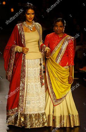 Indian Bollywood actress Neha Dhupia, left, along with village council head Vidya Vinayak Kule displays creations by Vikram Phadnis during the Lakme Fashion Week in Mumbai, India