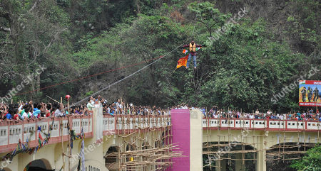 Graph, people watch as Indian Sailendra Nath Roy attempts to cross Teesta river suspended from a zip wire attached to his ponytail moments before his death in Siliguri, West Bengal state, India. Roy who was named a Guinness World Record holder in 2011 for travelling the farthest distance on a zip wire using hair died during the stunt Sunday when he suffered a heart attack