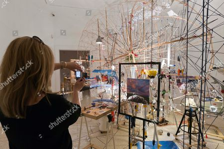 On a visitor photographs the installation 'Planetarium' part of the project 'Triple point' by artist Sarah Sze at the U.S. Pavilion during a press preview of the 55th edition of the Venice Biennale of Arts in Venice, northern Italy