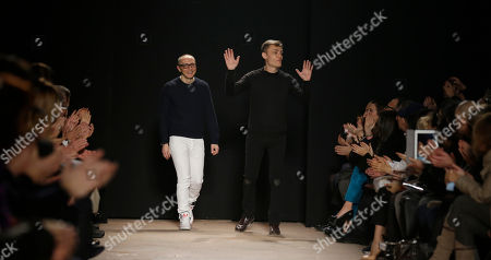 Italian fashion designers Tommaso Aquilani, left, and Roberto Rimondi are seen on the catwalk at the end of their women's Fall-Winter 2013-14 fashion show, part of the Milan Fashion Week, unveiled in Milan, Italy