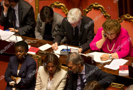 Front row from left; Integration Minister Cecile Kyenge, Health Minister Beatrice Lorenzin and Regional Affairs Minister Graziano Delrio, back row from left; Relations with Parliament Minister Dario Franceschini, Instruction and Research Minister Maria Chiara Carrozza, Culture Minister Massimo Bray and Justice Minister Anna Maria Cancellieri, wait ahead of a second confidence vote to confirm the government, in the Italian Senate in Rome, . Italy's new government easily passed its first confirmation vote Monday in Parliament after Premier Enrico Letta made concessions to his uneasy coalition allies, promising to ease part of a slate of austerity measures that have weighed on Italians impatient at the slow pace of economic recovery