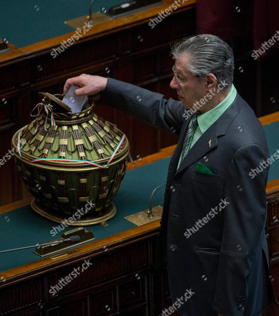 """Northern League lawmaker Umberto Bossi casts his ballot during the fifth round of voting to elect a new Italian head of state, at the Lower Chamber, in Rome .With a heavily polarized Parliament unable so far to agree on a new president for Italy, 87-year-old President Giorgio Napolitano yielded on Saturday to pleading from political leaders to be a candidate for a second term and quickly end an impasse which has thwarted efforts to form a government in the recession-mired country. Napolitano, citing his advanced age, had repeatedly refused to be a candidate for an unprecedented second seven-year term. But he said in a statement after lobbying from the leaders that he """"cannot help but take on the responsibility toward the nation"""