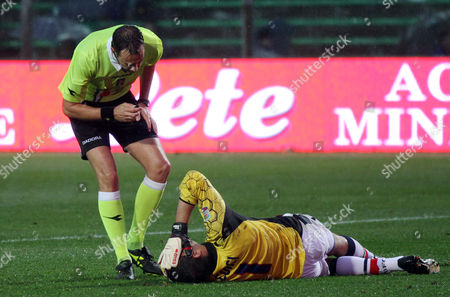 Gianluca Curci, Claudio Gavillucci Bologna's goalkeeper Gianluca Curci, bottom right, grimaces in pain as referee Claudio Gavillucci looks on during a Serie A soccer match against Atalanta in Bergamo, Italy, . The game ended 1-1 tie