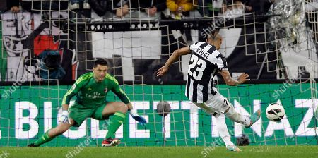 Juventus midfielder Arturo Vidal, of Chile, scores past AC Milan goalkeeper Marco Amelia on a penalty kick, during a Serie A soccer match, at the Juventus stadium in Turin, Italy