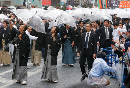 Kabuki actor Ebizo Ichikawa, left, Ennosuke Ichikawa, center, and other actors parade at Ginza shopping district in Tokyo, . Some 60 actors paraded in the rain Wednesday to newly renovated Tokyo theatre ahead of its official opening