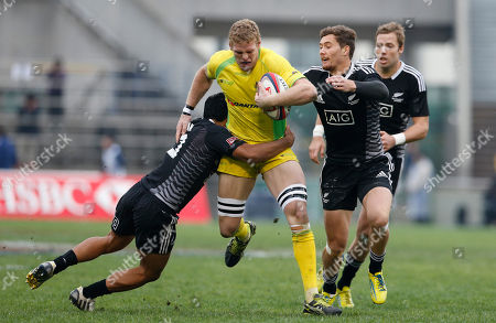 Tom Cusack, Rocky Kan, Gillies Kaka Tom Cusack, center, of Australia is tackled by Rocky Kan, left, and Gillies Kaka of New Zealand during their semifinal match of the Tokyo Sevens rugby tournament in Tokyo