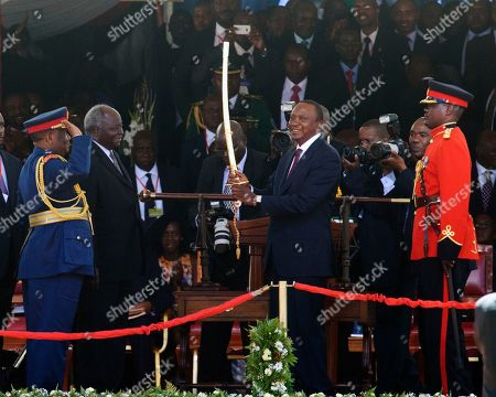 Stock Photo of President Uhuru Kenyatta, right, receives the sword of the Commander In Chief of the Kenya Armed Forces from outgoing president Mwai Kibaki, second left, at Moi International Sports Complex in Nairobi, Kenya, watched by Julius Karangi, Chief of Defence Forces Kenya, left. Uhuru Kenyatta was sworn in as the Kenya's fourth president Tuesday in a stadium filled with tens of thousands of Kenyans and a dozen African leaders