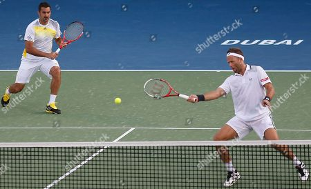 Robert Lindstedt, Nenad Zimonjic Robert Lindstedt of Sweden returns as teammate Nenad Zimonjic of Serbia looks on during the doubles final against Mahesh Bhupathi of India and partner Michael Llodra of France in the Dubai Duty Free Tennis Championships in Dubai, United Arab Emirates