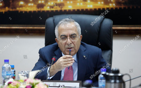 Outgoing Palestinian Prime Minister Salam Fayyad attends Palestinian government cabinet meeting in the West Bank city of Ramallah. The outgoing Palestinian prime minister is urging for new elections and says it's the only way to heal a bitter rift between the West Bank and Gaza Strip