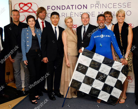 In this photo dated, Prince Albert II of Monaco, fourth right, and his wife Princess Charlene, fift left, pose for media with Norway alpine ski racer Aksel Lund Svindal, left, Agnes Falco Fondation General Secretary, second left, volley-ball player Bjorn Maaseide, third left, US actor Rick Yune, fourth left, free diver Pierre Frolla of Monaco, third right, ocean paddler Jamie Mitchell, second right, and US swimmer Dara Torres, right, during the presentation of ambassadors for Princess Charlene Foundation at the Yacht Club, in Monaco