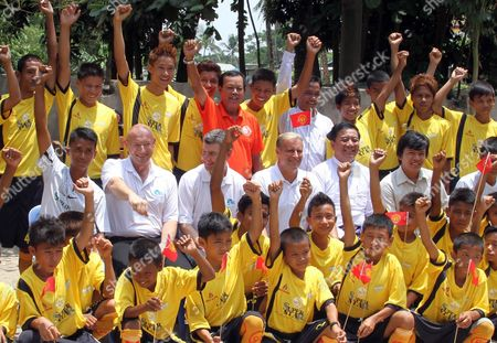 Former Manchester United players Clayton Blackmore, fourth from left, and Denis Irwin, third from left, pose for photo along school soccer team as they visit a monastic school, in Yangon, Myanmar