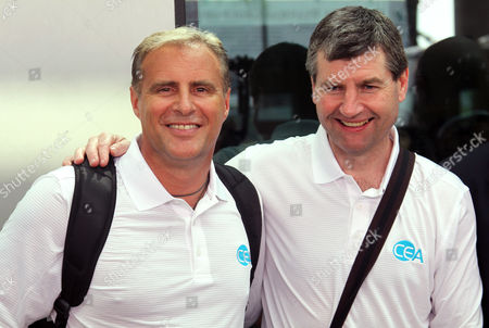 Former Manchester United players Clayton Blackmore, left, and Denis Irwin, right, pose for photos upon their arrival at Yangon International Airport to play friendly match, in Yangon, Myanmar
