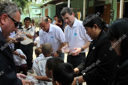 Clayton Blackmore, center left, and Denis Irwin, centrr right, former Manchester United players, give food to school children as they visit a monastic school, in Yangon, Myanmar