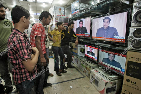 Pakistani men watch a TV broadcast of Pakistani Prime Minister Raja Pervaiz Ashraf addressing the country, at an electronic shop in Karachi, Pakistan. . Pakistan's government is passing a remarkable milestone in a country that has faced three military coups -- it's the first democratically elected body to finish its term