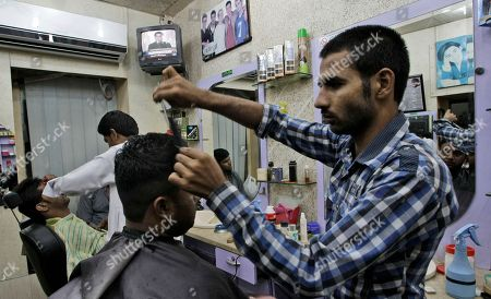 A TV broadcast showing Pakistani Prime Minister Raja Pervaiz Ashraf addressing the country, airs in the background at a barber shop in Karachi, Pakistan. . Pakistan's government is passing a remarkable milestone in a country that has faced three military coups -- it's the first democratically elected body to finish its term