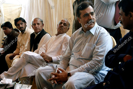 Pakistan's former Prime Minister Yousuf Raza Gilani, second right, sits with people visiting his residence to console over his son's abduction in Multan, Pakistan, . Gunmen attacked an election rally in Pakistan's southern Punjab province on Thursday and abducted Ali Haider Gilani, son of a former prime minister, intensifying what has already been a violent run-up to Saturday's nationwide elections