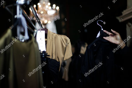 An employee hangs a dress backstage prior to Dutch fashion designer Steffie Christiaens' ready to wear Fall/Winter 2013-2014 collection, in Paris