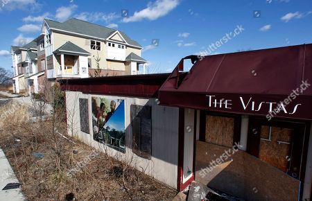 In this March 14, 2013 photo, the dilapidated remains of the failed The Vistas condominium project's model homes are seen overlooking the Passaic River, near the Great Falls in Paterson, N.J. On, Paterson Mayor Jeffery Jones is floating the idea of building a 22-story hotel complex on the site of the failed condo project, on cliffs near the Great Falls