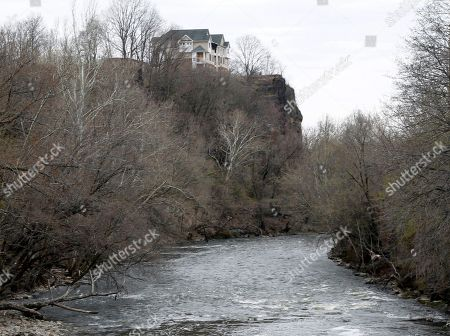 In this April 13, 2013, photo, the dilapidated remains of the failed The Vistas condominium project's model homes are seen overlooking the Passaic River, near the Great Falls in Paterson, N.J. On, Paterson Mayor Jeffery Jones is floating the idea of building a 22-story hotel complex on the site of the failed condo project