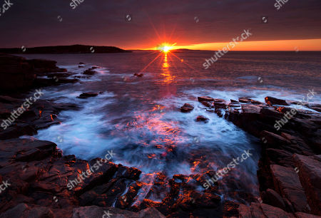"""The sun's rays strike the rocky coast of Acadia National Park on Mt. Desert Island in Maine. David Rockefeller, whose father John Rockefeller Jr., built the carriage roads that are now part of Acadia National Park, turns 100 on June 12, 2015. He will celebrate by transferring his family property at Little Long Pond in Seal Harbor to the Mount Desert Island & Garden Preserve, describing it as a """"gift to all the people of Maine"""