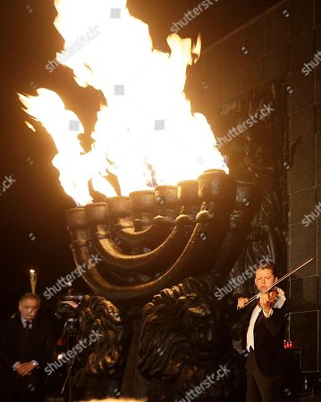 Stock Picture of Julian Rachlin Julian Rachlin, right, the first violinist with the Israel Philharmonic Orchestra, plays a Bach sarabande in front of the monument to the fighters of the Warsaw ghetto uprising in Warsaw, Poland, on . The performance was part of an evening of commemorations on the eve of the 70th anniversary of the outbreak of the 1943 revolt