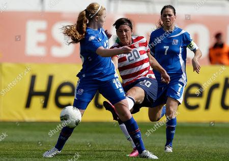 Abby Wambach of the U.S. attempts a shot at goal between Iceland's Glodis Perla Viggosdottir, left, and Sara Bjork Gunnarsdottir, right, during their Algarve Cup women's soccer match in Albufeira, southern Portugal