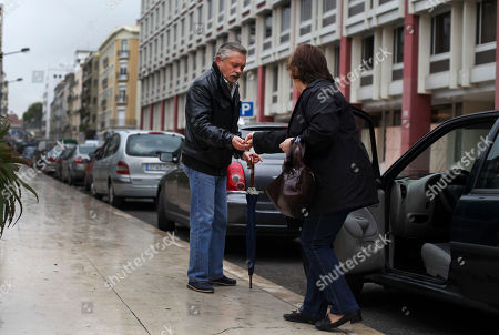Celestino Ribeiro, left, 56, who has been unemployed for three years, receives some coins after helping a woman to park her car outside the Bank of Portugal offices in Lisbon, . Ribeiro, who worked as a painter in the construction sector for 41 years, receives euros 176 (USD 229) a month in benefits. Inspectors from Portugal's bailout lenders are back in Lisbon to see how the government intends to plug a euro 1.3 billion (USD 1.7 billion) hole in its state budget