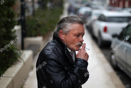 Celestino Ribeiro, 56, who has been unemployed for three years, smokes a cigarette as he works helping people to park their car outside the Bank of Portugal offices in Lisbon, . Ribeiro, who worked as a painter in the construction sector for 41 years, receives euros 176 (USD 229) a month in benefits. Inspectors from Portugal's bailout lenders are back in Lisbon to see how the government intends to plug a euro 1.3 billion (USD 1.7 billion) hole in its state budget