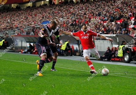Benfica's Carlos Martins, right, vies for the ball with Bordeaux's Julien Faubert, left, and Jaroslav Plasil, from Czech Republic, center background, during their Europa League round of 16 first leg soccer match at Benfica's Luz stadium in Lisbon