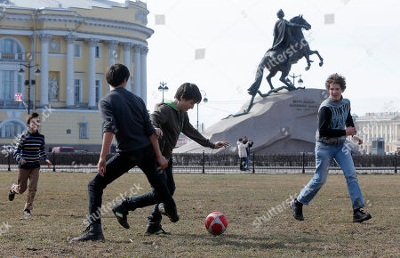Children play football in St.Petersburg, Russia, with one of the city landmarks, equestrian statue of Peter the Great by Etienne Maurice Falconet, seen in the background