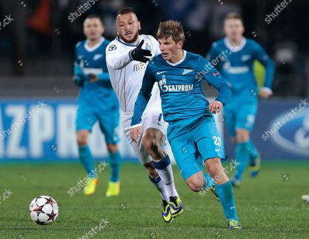Porto's Nabil Ghilas, left, challenges Zenit's Andrey Arshavin during the Champions League group G soccer match between Zenit and Porto at Petrovsky stadium in St.Petersburg, Russia, on