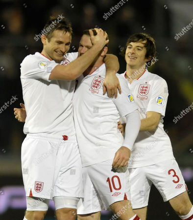 England's Wayne Rooney, center, celebrates with his teammates Frank Lampard, left, and Leighton Baines, after scoring, during a World Cup qualifying group H soccer match between England and San Marino at the Serravalle stadium, Italy