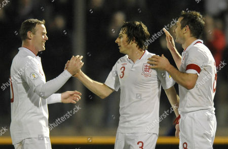 England's Wayne Rooney, left, celebrates with his teammates Leighton Baines, center, and Frank Lampard, after scoring, during a World Cup qualifying group H soccer match between England and San Marino at the Serravalle stadium, Italy