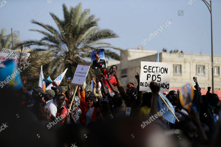 People cheer as more than a thousand people rallied to call for the release of Karim Wade, who was arrested last week on corruption charges, in Dakar, Senegal, . The sign at right reads 'PDS (Senegalese Democratic Party) - Diamnadio Section.' Authorities charged Karim Wade, the son of Senegal's former president Abdoulaye Wade, with illicit enrichment Wednesday, April 17, following a months-long investigation into how he allegedly amassed a fortune of more than US dlrs 1.3 billion
