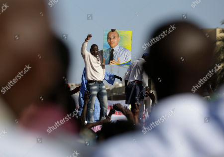 An opposition party militant holds up a poster of Karim Wade, as more than a thousand people rallied to call for the release of the former president's son, who was arrested last week on corruption charges, in Dakar, Senegal, . Authorities charged the son of Senegal's former president Abdoulaye Wade with illicit enrichment Wednesday, April 17, following a months-long investigation into how he amassed a fortune of more than $1.3 billion