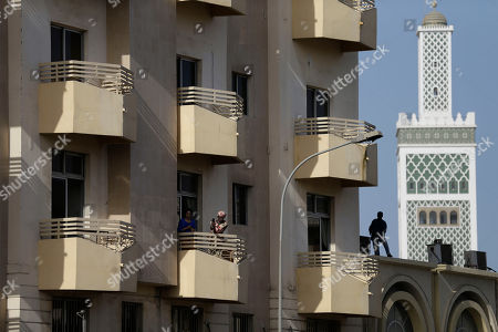 A woman takes pictures from a balcony, as more than a thousand people rallied below to call for the release of Karim Wade, who was arrested last week on corruption charges, in Dakar, Senegal, . Authorities charged the son of Senegal's former president Abdoulaye Wade with illicit enrichment Wednesday, April 17, following a months-long investigation into how he amassed a fortune of more than $1.3 billion