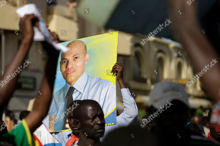 An opposition party militant holds up a poster of Karim Wade, as more than a thousand people rallied to call for the release of the former president's son, who was arrested last week on corruption charges in Dakar, Senegal, . Authorities charged Karim Wade, the son of Senegal's former president Abdoulaye Wade, with illicit enrichment Wednesday, April 17, following a months-long investigation into how he allegedly amassed a fortune of more than US dlrs 1.3 billion